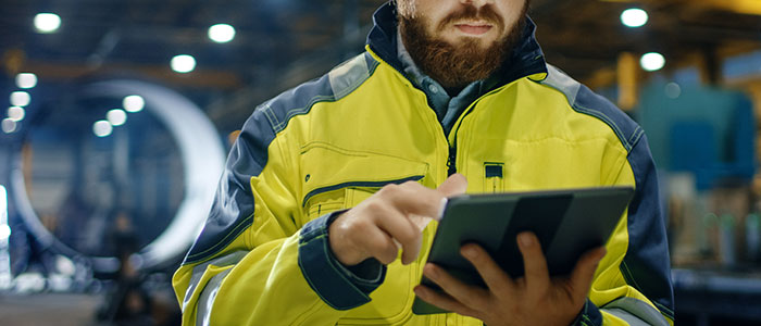 Warehouse worker with scruffy bear analyze his digital tablet, ensuring the warehouse floor is safe post Job Safety Analysis