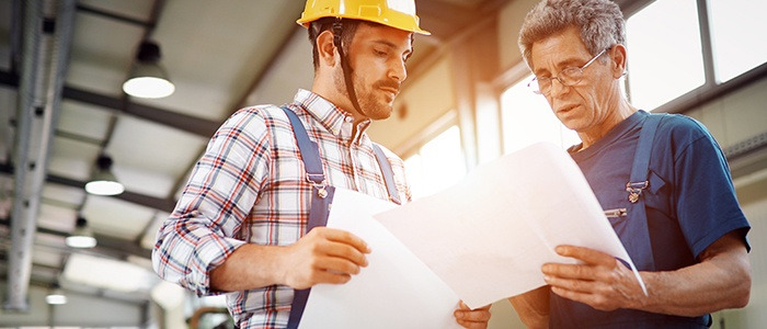 Two men intensely scrutinizing the list of import tasks within a situated Job Safety Analysis